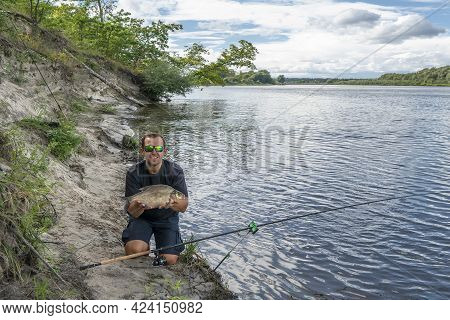 Feeder Fishing. Fisherman With Big Bream Fish In Hands And Tackle At Wild River Shore