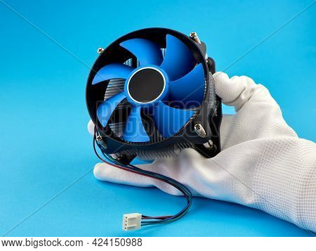 Pc Cpu Cooler With Thermal Paste. A Hand Wearing A White Glove Holds The Cpu Cooler Of The Computer
