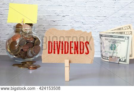 Hand Putting Coin In Jar Word Dividend With Money Stack, Concept Business Finance And Investment.