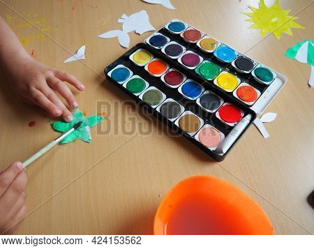 Desktop With Drawing Tools. Set Of Watercolor Paints. Paper-cut, Painted Fish Figurines. View From A
