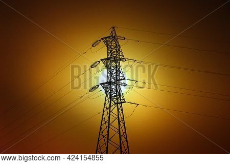 Electric Power Transmission Tower In Backlight And Bright Sun