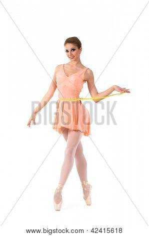 Young and beautiful ballerina dancing with a measuring tape over white background