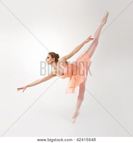 Young and beautiful ballerina dancing over white background