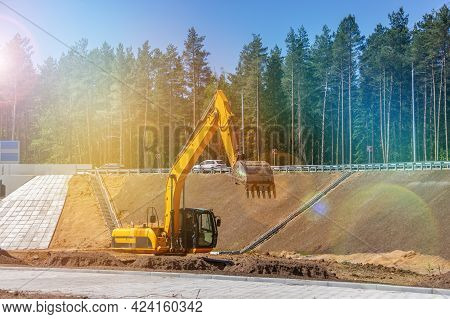 The Excavator Prepares The Site For The Construction Of The Road. Orange Construction Machinery. Ear