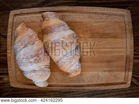 Two Croissants On A Wooden Cutting Board.