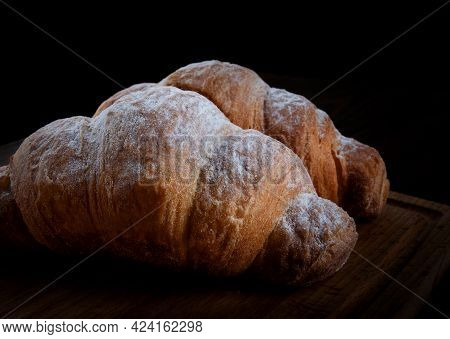 Two Croissants On A Dark Background. French Pastries.