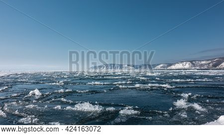 Ice Drift On The River. Blue Ice Floes And Melted Snow On The Surface Of The Water. Snow-covered Mou