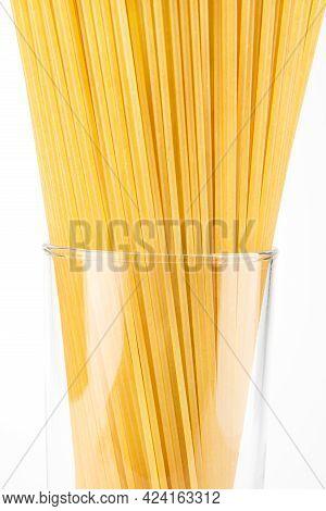 Yellow Long Spaghetti On White Background. Thin Pasta Arranged In Rows. Yellow Italian Pasta. Raw Sp
