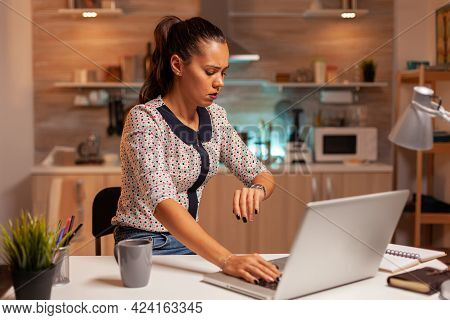 Businesswoman Checking Time On Watch While Working From Home. Employee Using Modern Technology At Mi