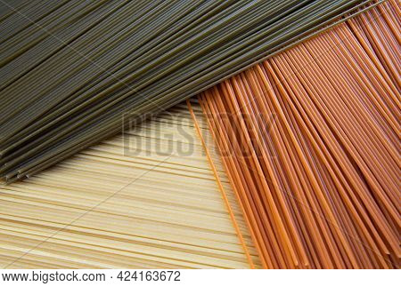 Background From Multi-colored Pasta. The Long Pasta In Three Colors Is Beautifully Laid Out. Yellow