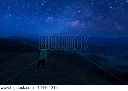 Colorful Night Sky With Stars And Silhouette Of A Standing Man On The Stone. Blue Milky Way With Man