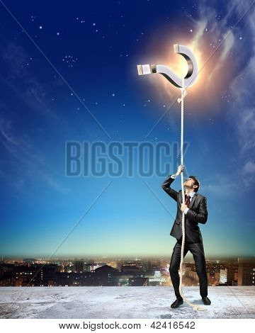 Image of businessman climbing rope attached to question sign aloft against city background poster