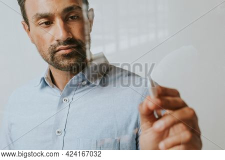 Mature man writing on an invisible screen