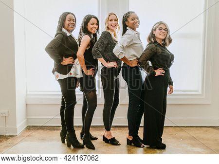 Happy empowering businesswomen by a window