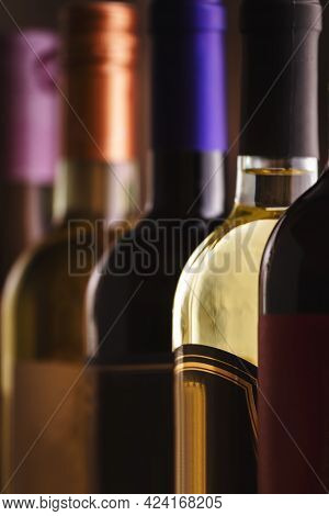 Wine Bottles Collection Row In Wine Cellar, Winery Basement, Bar Or Shop On Dark Wooden Background