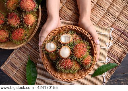 Woman Hand Holding Ripe Rambutan Fruit In A Basket, Rambutan Is Tropical Fruit And Native Southeast