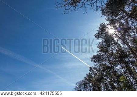 A Plume Of Steam Visible In The Blue Sky Behind A Passing Plane As An Increasingly Common Sight Sinc