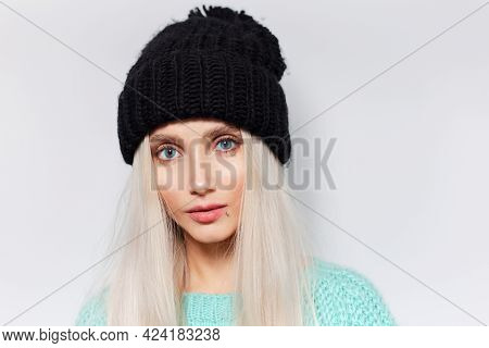 Portrait Of Pretty Blonde Girl With Blue Eyes On White Background, Wearing Black Hat And Cyan Sweate
