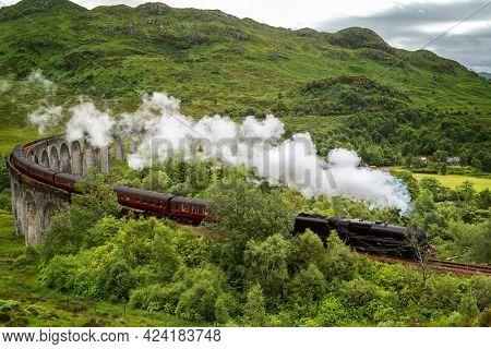 A vintage steam train crosses the Glenfinnan Viaduct at Loch Shiel, Scottish Highlands, UK. The West Highland line runs through Inverness-shire, Scotland.