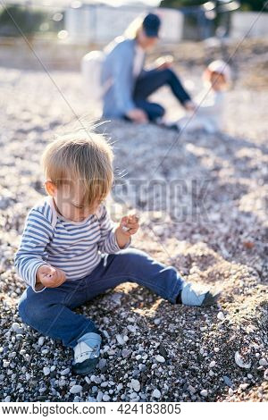 Kid Sits On A Pebble Beach With Hands Full Of Pebbles