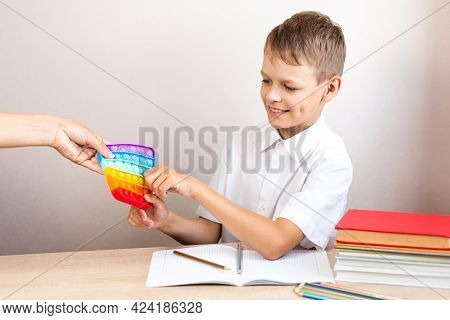A Child In A White Shirt Sits At A Table And Takes An Eternal Bubble From A Woman's Hands To Play Wi