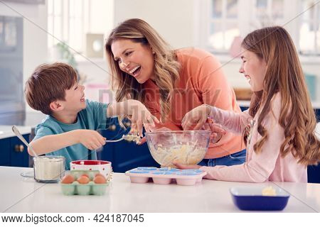 Children Putting Cake Mixture On Mother's Nose In Kitchen As They Have Fun Baking Cakes Together