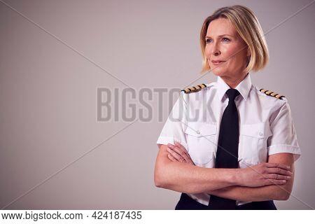 Studio Portrait Of Serious Mature Female Airline Pilot Against Plain Background