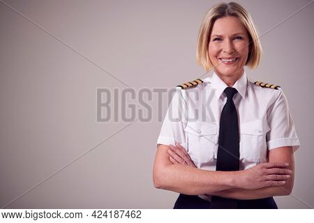 Studio Portrait Of Smiling Mature Female Airline Pilot Against Plain Background