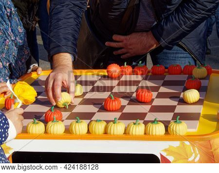 Checkers In The Form Of Pumpkins On The Checkerboard And The Hand Holding The Checker To Make A Move