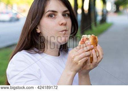 Brunette Woman Overeats On A Burger On The Street. Gluttony, Excess Calories, And Bulimia.