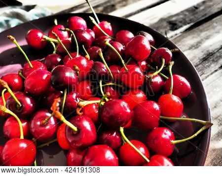 Cherry Background. Juicy Ripe Delicious Cherry Or Sweet Cherry Close-up Side View On A Dark Plate An