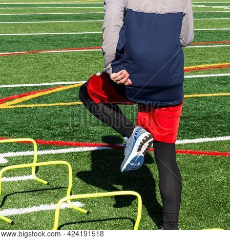 Rear View Of A High School Track Runner Is Stepping Over One Foot Mini Hurdles On A Turf Field On A