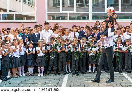 Krasnodar, Russia - September 1, 2018: Senior Pupil Carries First-former Girl Ringing With Golden Be