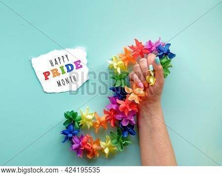 Lgbtq Community Pride Month Text On Paper Scrap. Hand With Fake Nails In Colors Of The Rainbow Holds