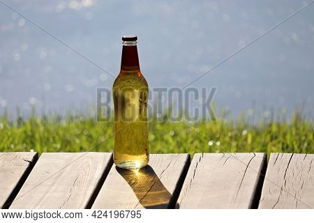 Glass Bottle Of Light Beer On Wooden Boards On A Beach. Summer Holidays, Cool Drink For Thirst Quenc