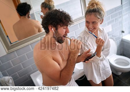 young man looking at his cell phone with headphones in his ears, brushing teeth with his female partner watching at him, smiling. Valentines  day