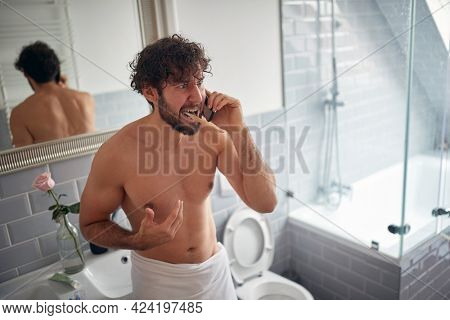bad news in the morning concept. Young caucasian guy yelling after receiving bad news on his cell phone while brushing his teeth in the bathroom