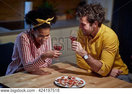 valentine, date, at home, lockdown concept. young adult multiethnic couple laughing, drinking wine with canapes at home, talking, laughing.