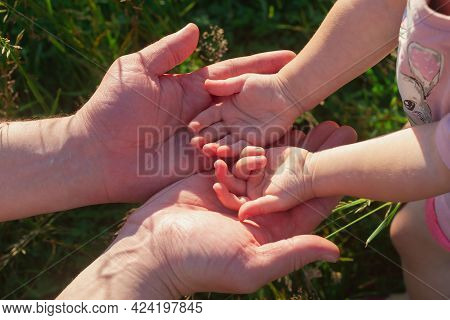 Small Hands Of The Baby In The Big Hands Of The Father, The Concept Of Fatherhood And Family.