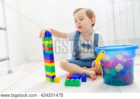 A Child With A Constructor At Home, A Cute Boy Plays Or Collects A Colored Constructor