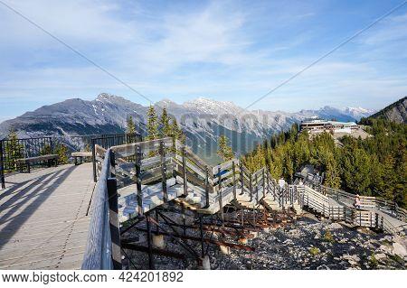 Banff, Canada - July 2, 2014: Visitors Walk The Wooden Boardwalk On Top Of Sulphur Mountain Between