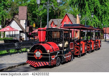 Mogosoaia, Romania - 7 May 2021: Vivid Red Train For Children In Front Of Colourful Wooden Houses In