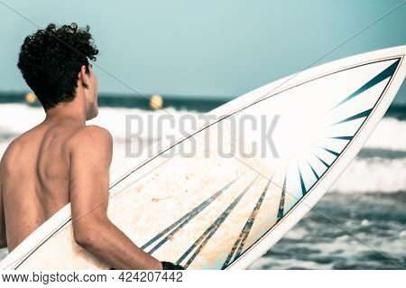 Closeup Shot Of A Surfer Holding A Surfboard At The Beach. A Surfer With His Surfboard Looking To Th