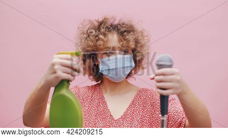 Girl Spraying Water On The Microphone. Attractive Young Girl Wearing A Face Mask Holding A Spray Bot