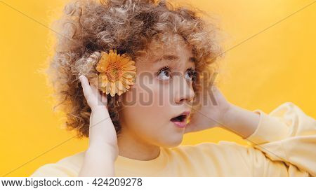 Beautiful Young Girl With A Flower On Her Ear Trying To Listen To Someone With Both Hands On Her Ear