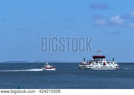 Waddensea, Netherlands-april 26, 2021: The Fast Ferry And The Car Ferry Boat With Passengers Sailing
