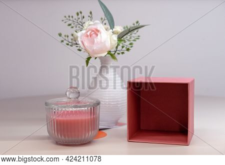 Pink Scented Candle In A Glass Candlestick And Vase With A Flower.