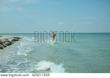 A Man Runs Along The Sea Surf Along The Coast. Splashes Of Water Surround The Silhouette Of A Man.