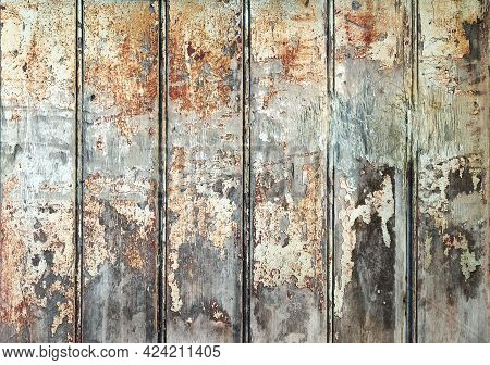 Vertical Slats Of Heavily Weathered Wood. Wooden Panels With Peeling And Worn Paint