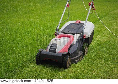Electric Lawn Mower On Front Yard. Lawn Mower In Garden.